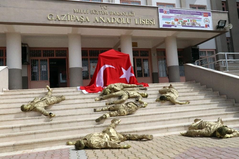 Bronz görünümünde asker kılığındaki öğrenciler, okul merdiveninde şehit düşmüş halde yattılar